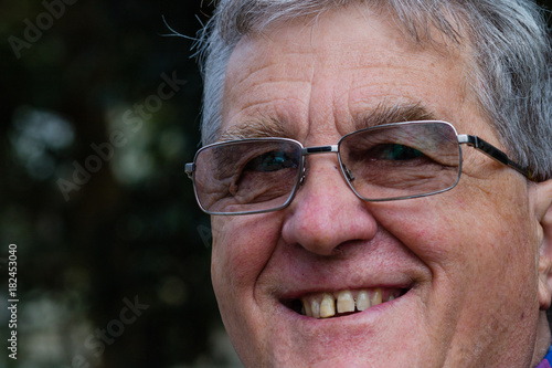 Photo  An older man wearing glasses and smiling at the camera.