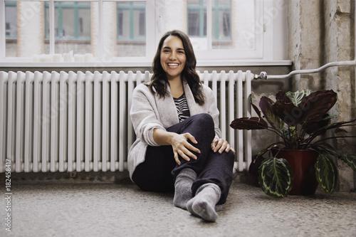 Fotografie, Obraz  Junge Frau sitzt entspannt auf dem Boden