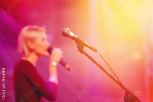 Plakat Mikrofon do karaoke. Zbliżenie światła podsufitki, sylwetka piosenkarza