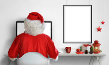 Santa Claus Work On Computer. Picture Poster Frame On Wall With Isolated Blank Space For Mockup, Adding Greeting Text. Christmas Decorations On Table.