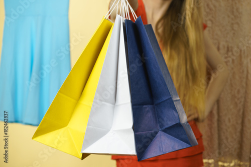 Photo Stands Unrecognizable woman in shop picking summer outfit