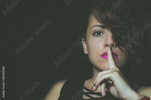 Fotografie, Obraz  Woman showing silence shh gesture with index finger close to mouth asking for be