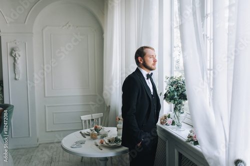 Fotografie, Obraz  A gentleman in a suit looks out the window. Wedding concept