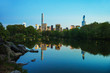 Midtown Manhattan skyline reflected from water Central Park NYC