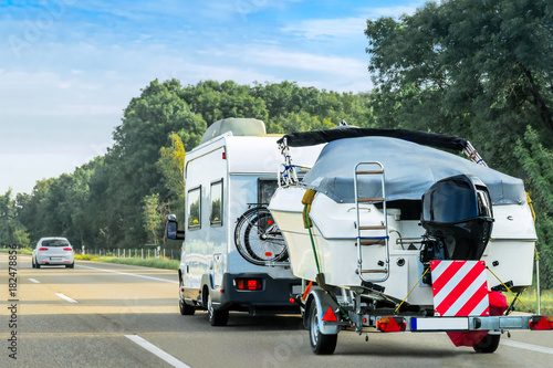 Fototapeta  Caravan and trailer for motor boats on road in Switzerland