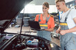 Experienced female auto mechanic checking the engine error codes scanned by a car diagnostic software while standing next to a motivated apprentice
