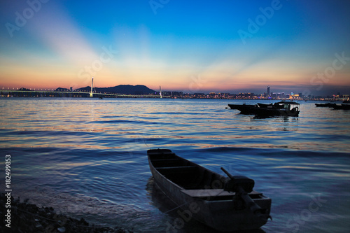 Spoed Foto op Canvas Zee zonsondergang Fisherman boat under the sun set and the ray from the skyline in summer at chinese fishing village in hong kong, night scenes from hong kong to shenzhen coast at Ha Pak Nai, Yuen Long