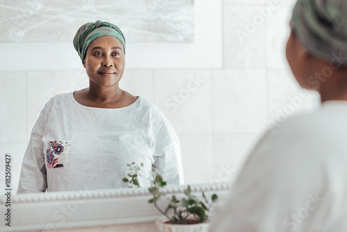 Young African woman wearing a headscarf looking in the mirror Wallpaper Mural