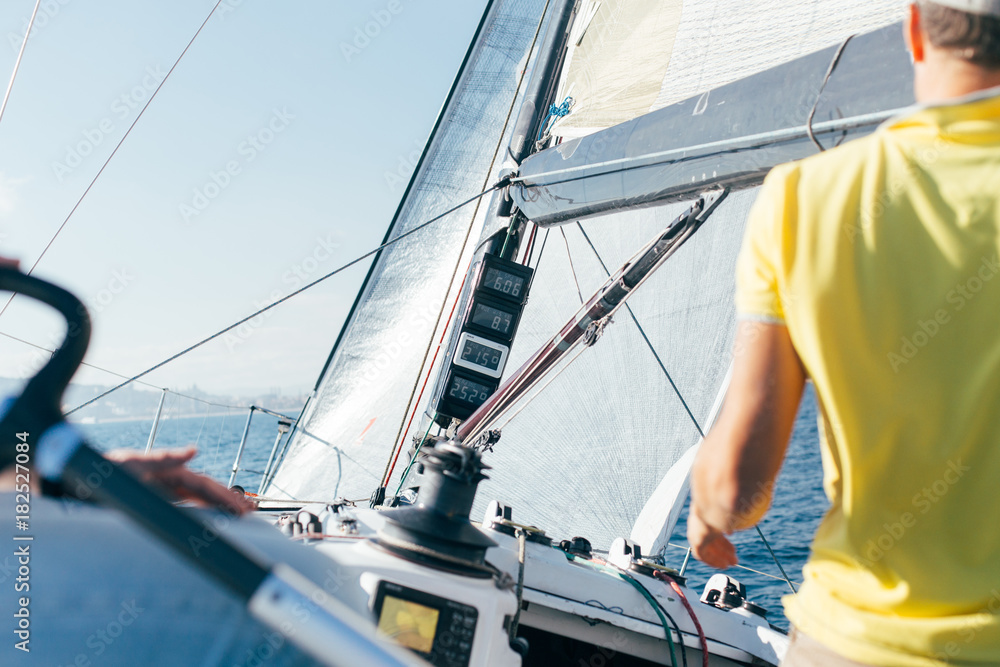 Fototapety, obrazy: Professional sailor or yachtsowner controls sailboat with mainsail and spinnaker up, by observing data and information from devices on mast, wind speed and power