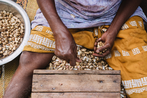 Crop person shelling nuts