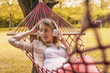 season, technology and people concept - beautiful happy young woman with headphones listening to music Woman wearing headphones. Young woman listening to music on smart phone. Girl relaxing in hammock