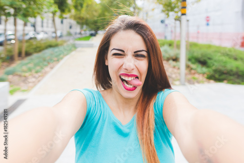 Photo self portrait young woman mixed race outdoors tongue sticking out - happiness, h