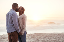 Romantic Young African Couple Kissing On A Beach At Sunset
