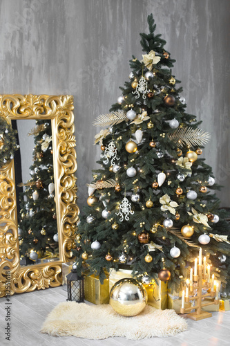Big silver and gold decorated christmas tree with gifts in luxury interior. New year at home.