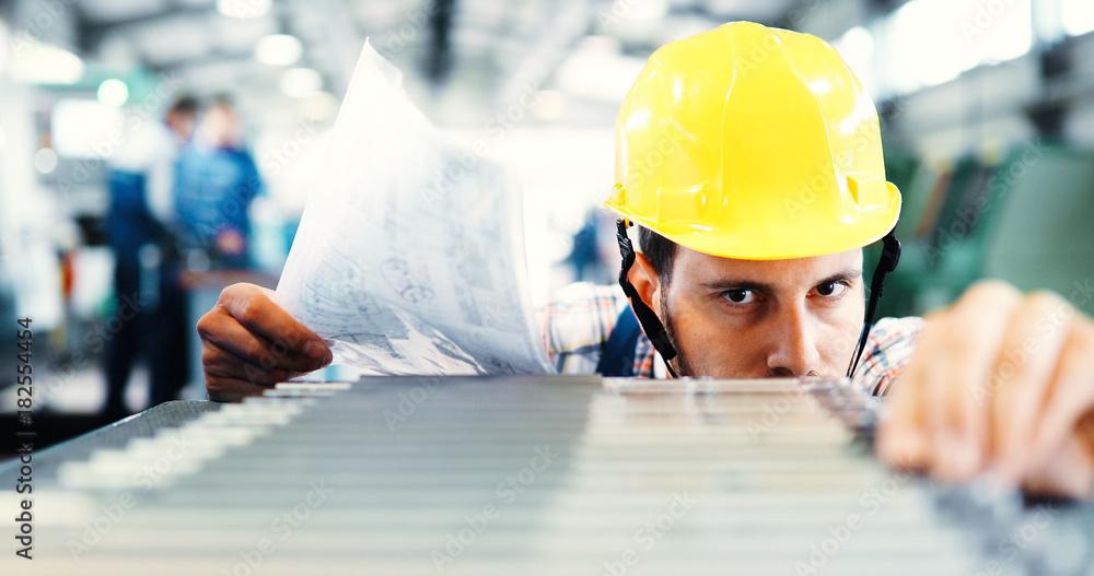 Fototapeta Industry Worker entering data in CNC machine at factory