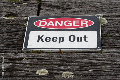 Poster  Danger, keep out warning sign over old weathered rustic wooden t