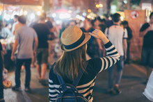 Young Asian Woman Traveler Backpacker With Hat And Bag Traveling To Chiang Mai Night Walk Street Market At Chiang Mai Province, Thailand.
