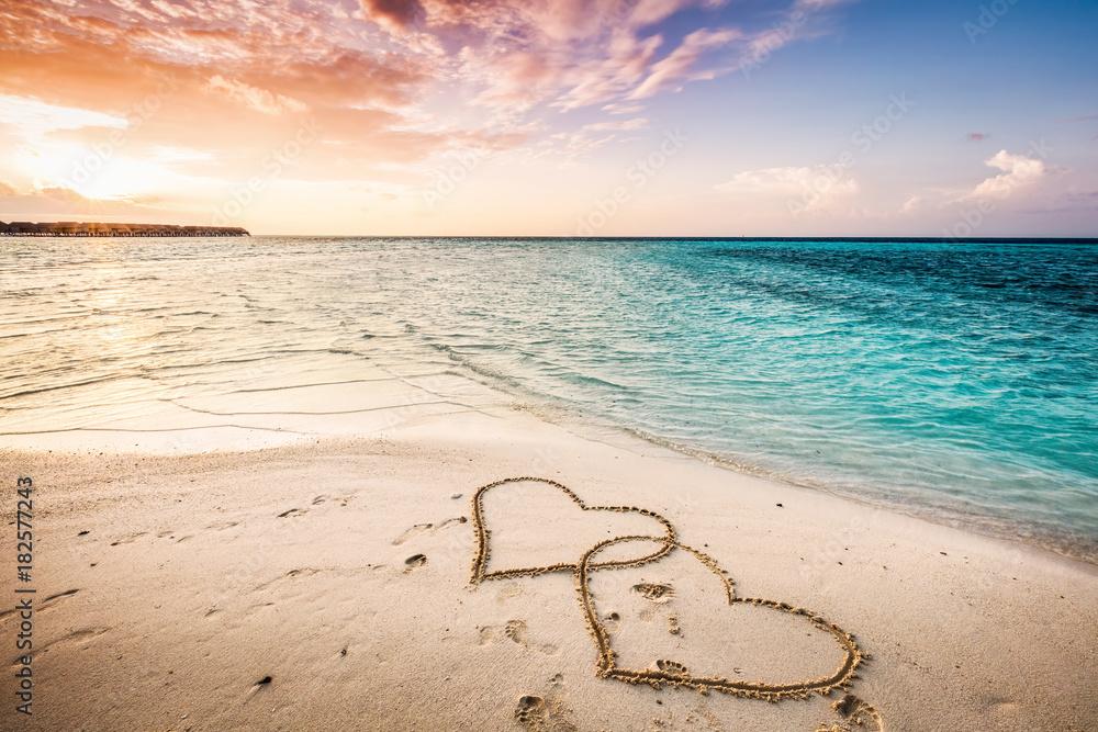 Fototapeta Two hearts drawn on a sandy beach by the sea.