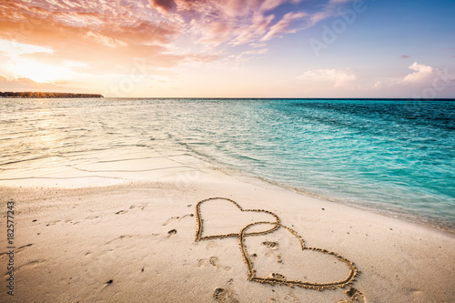 Two hearts drawn on a sandy beach by the sea.