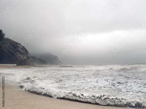 Stürmische Meerlandschaft Küste an einem stürmischen Tag mit Felsen Bergen und Meer im Hintergrund