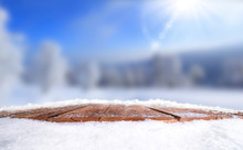 Wooden Table, Bench Covered In Snow With A Christmass, Wintery And Snowy Background With Space To Add Products And Text.