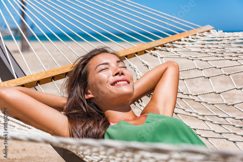 Relaxing woman sleeping on hammock in the tropical sun. Asian girl resting lying down in resort lounger laid back enjoying suntan in Caribbean travel holidays.