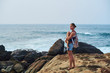 young alone girl standing on a stone cliff close to ocean