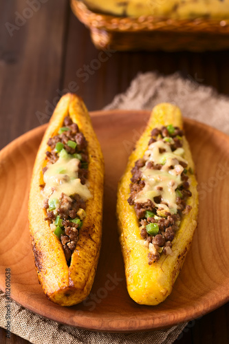 Baked ripe plantain stuffed with mincemeat, olive, capsicum, onion, traditional dish in Central America called Canoa de Platano (Plantain Canoe) (Selective Focus one third into the image)