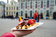 canvas print picture - Belgium waffle with chocolate sauce and strawberries, Bruges city background