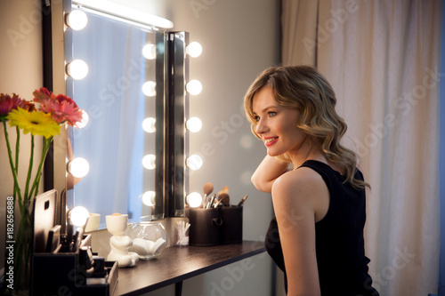 Valokuva  Smiling blonde girl primp at the mirror with lamps in the beauty studio