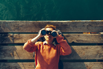 Young Girl Lies On A Pier Near The Sea And Looks Through Binoculars. Travel Search Journey Concept