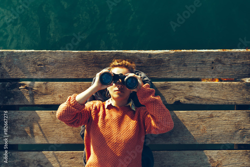 Fototapeta Young Girl Lies On A Pier Near The Sea And Looks Through Binoculars. Travel Search Journey Concept obraz