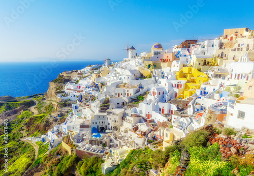 Fototapeta Greece, Santorini. Amazing view from famous sunset point on island in Aegean sea -  Santorini over Oia - Ia village at the slope of volcano. Famous windmills and traditional greek white architecture. obraz