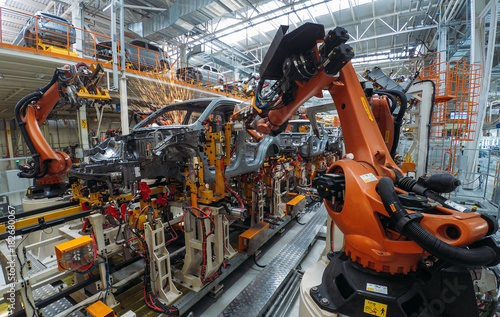 Photo  Automobile plant, welding process, modern production of cars, robot equipment, automated production line