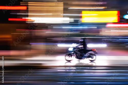 Fotomural Motocicletta che sfreccia veloce di notte per le vie con luci colorate di una  g