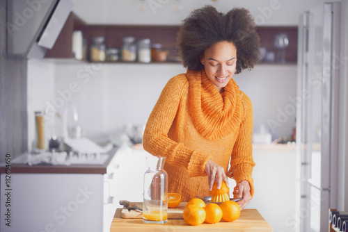 Foto  Mixed race woman squeezing orange fruit and making the juice while standing in m