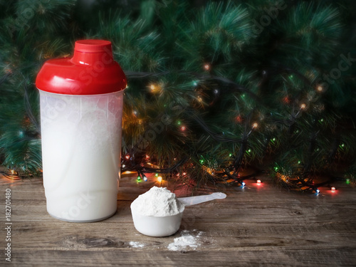 Christmas Sports Background.Whey Protein Shaker And Scoop On Christmas Background