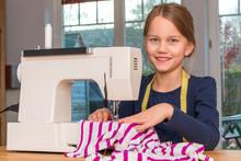Ein 8 Jahre Altes Mädchen Näht Mit Einer Nähmaschine Einen Gestreiften Stoff Zu Hause, Porträt