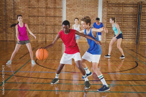 Fotografie, Obraz  High school kids playing basketball in the court