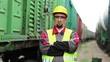 Railway worker looks at the camera. Railwayman stands between goods trains on freight station