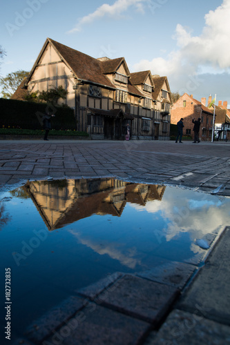 Shakespeare birthplace building reflected in large puddle Canvas Print