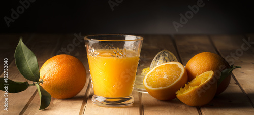 Poster Sap Glass with orange juice on the wooden table
