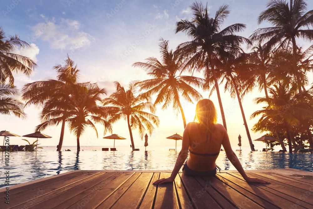 Fototapeta Woman enjoying vacation holidays luxurious beachfront hotel resort swimming pool