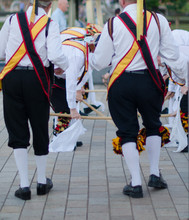 Traditional Morris Men Dancing In The UK With Sticks Bells And Musical Instrument