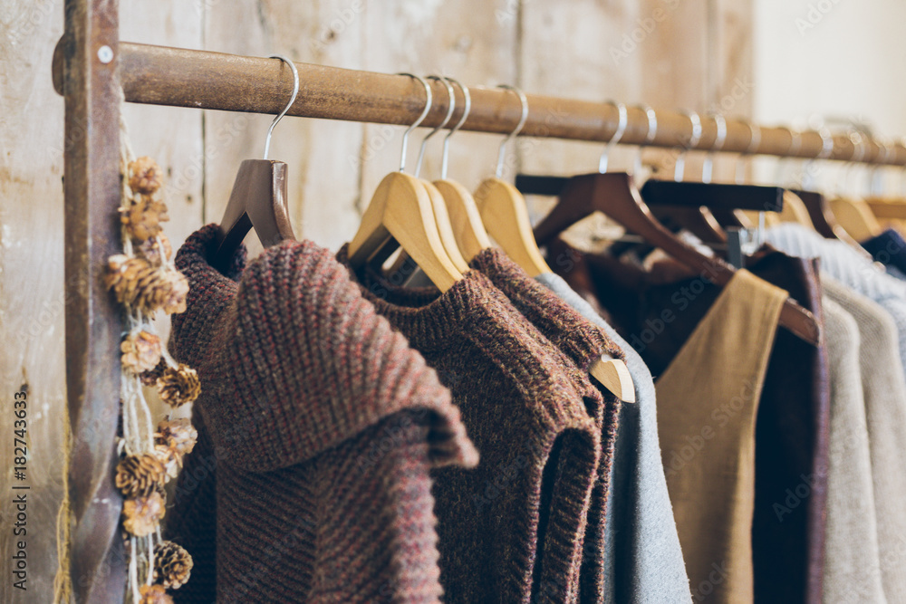 Fototapeta Conscious / ethical  fashion trend concept.  Warm winter ladies clothes collection with knitted jumpers, dresses and cardigans on wooden hangers.