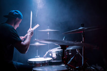 Drummer In A Cap And Headphones Plays Drums At A Concert Under Blue Light In A Smoke
