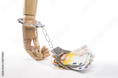 Fotografía  Hand chained to banknotes with handcuffs