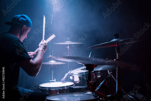 Fotografija Drummer in a cap and headphones plays drums at a concert under blue light in a s