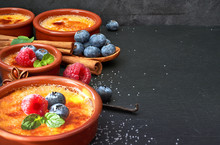 Creme Brulee With Berries And Ingredients On Dark Stone, Space