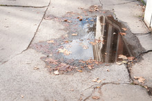 Pond Of Rain Water In The Hole On The Damaged Sidewalk